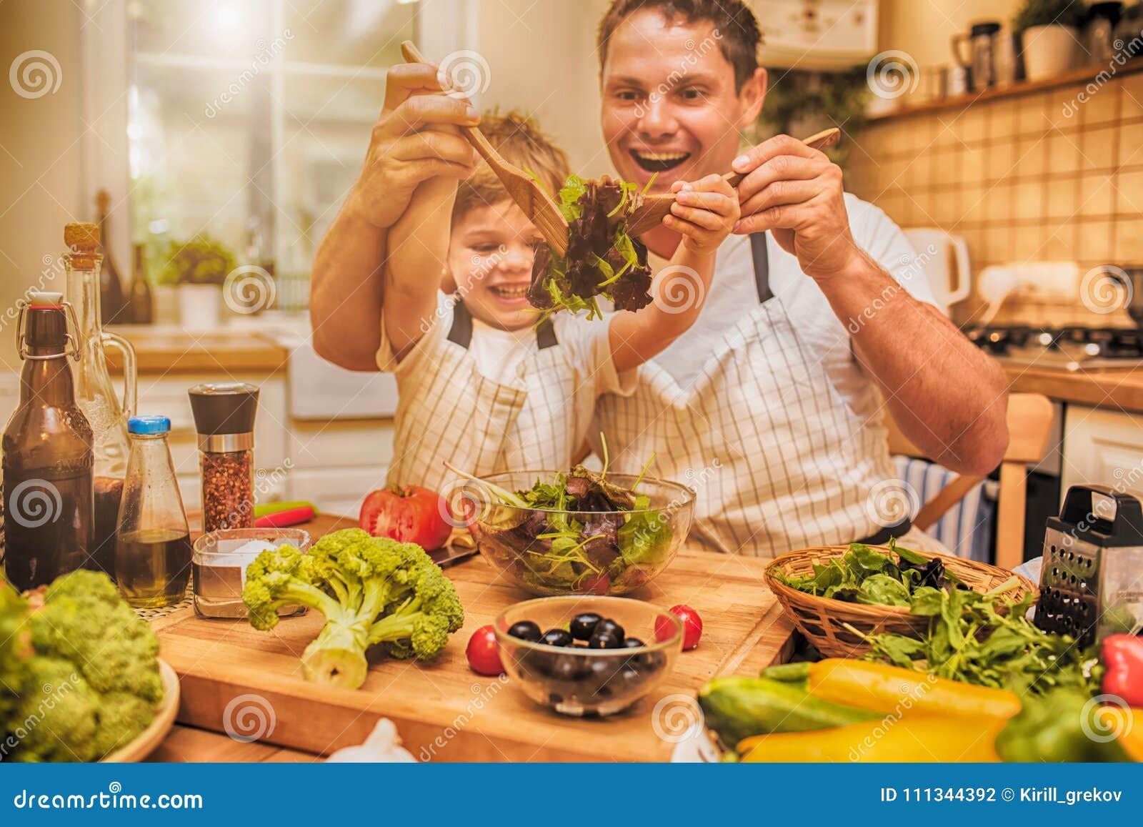 Keuken Voor Weinig : Mens het koken op de keuken met weinig zoon stock foto