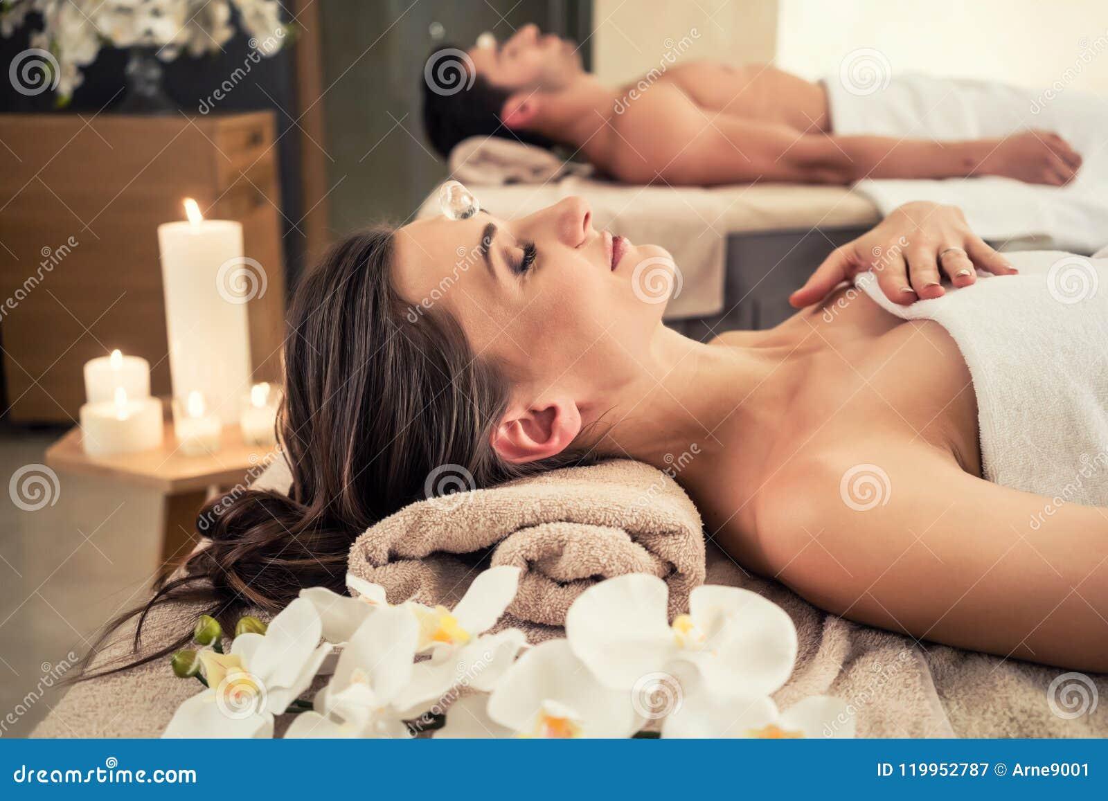 Mens het ontspannen met zijn partner op massagebedden op wellnesscentrum