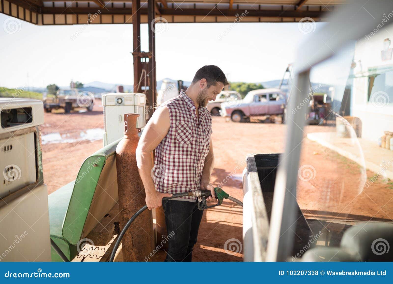 Mens het vullen benzine in auto bij benzinepomp