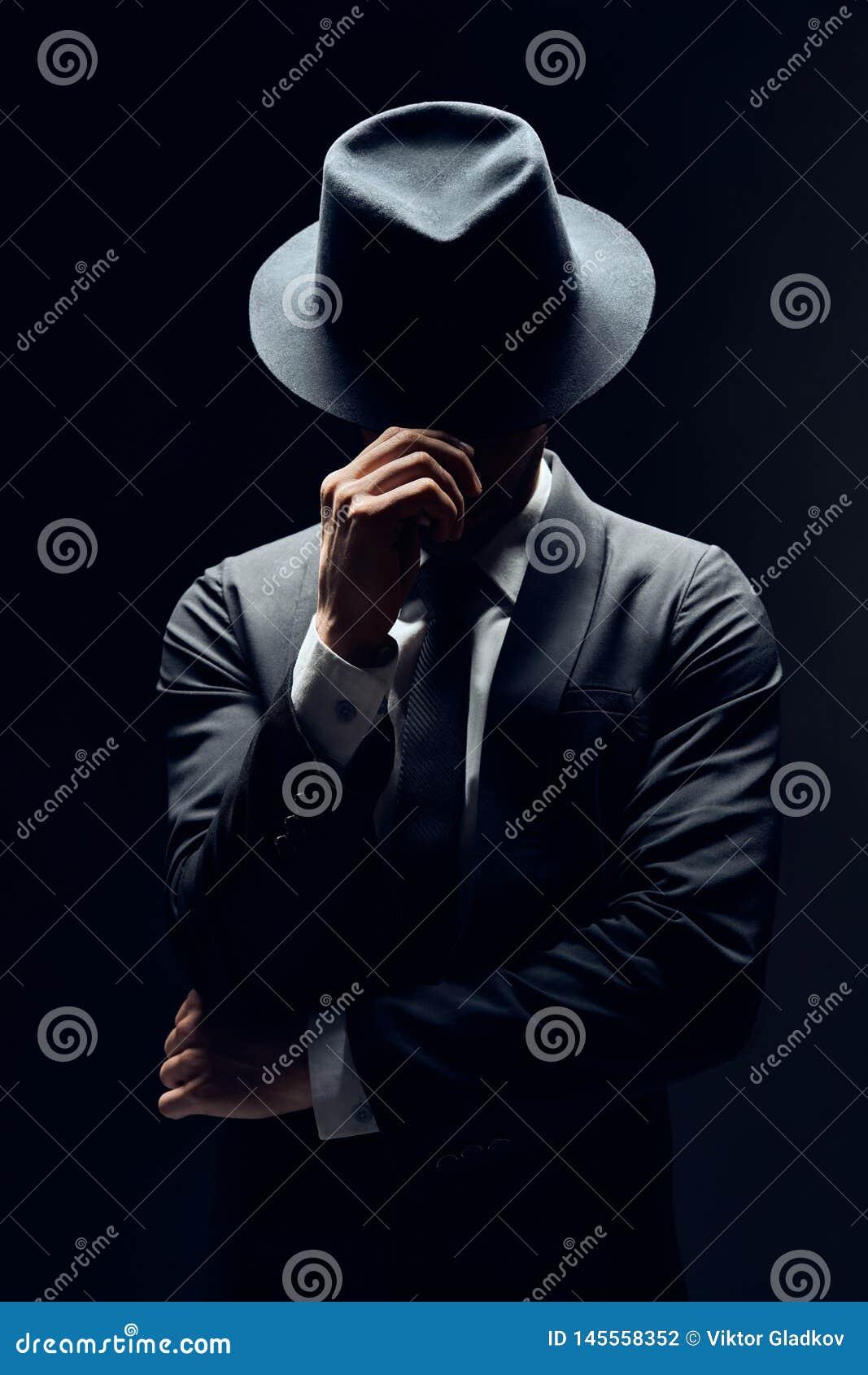 Mens in kostuum verbergend gezicht achter zijn die hoed op donkere achtergrond wordt ge?soleerd