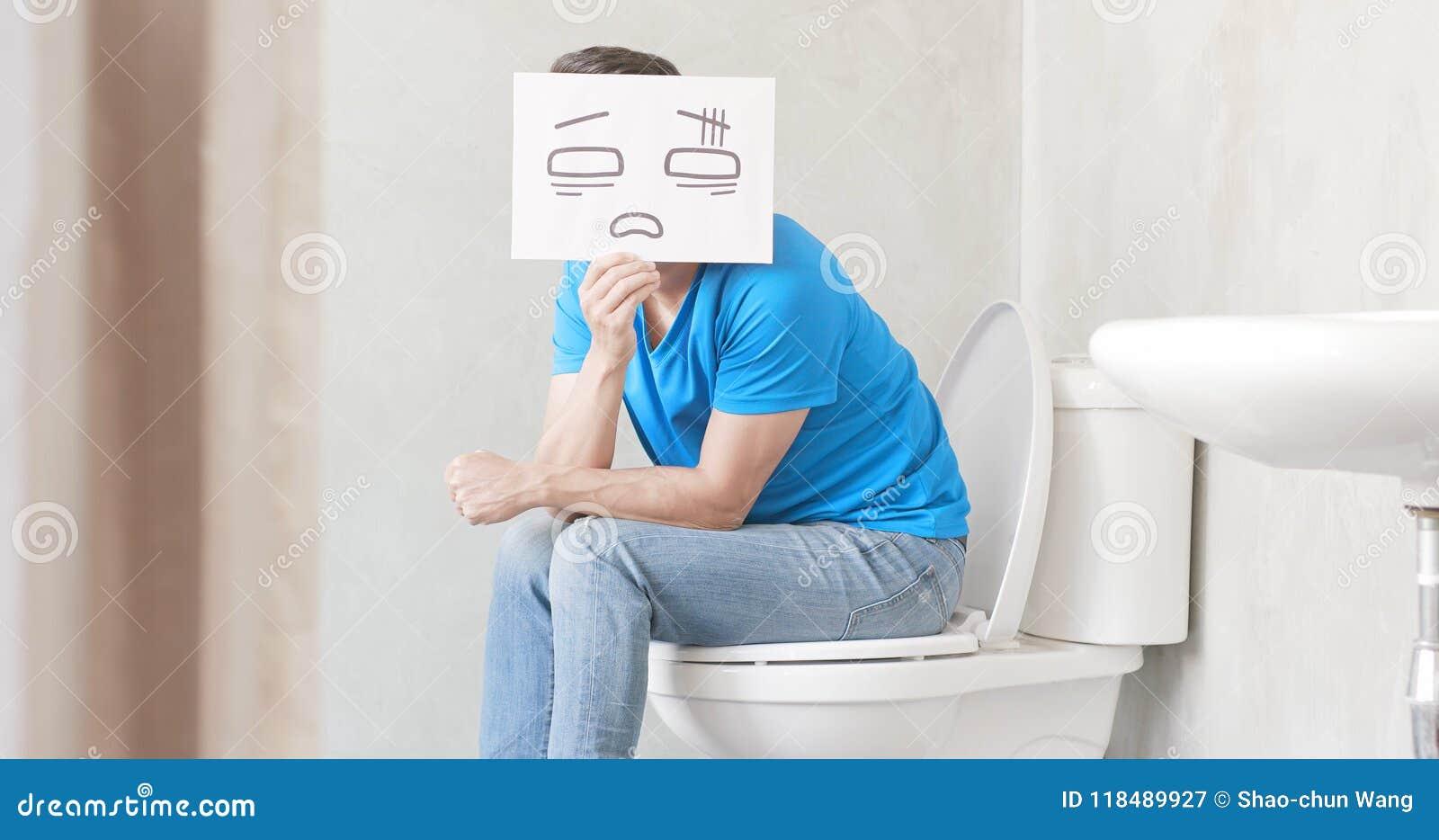 Mens met constipatie op toilet