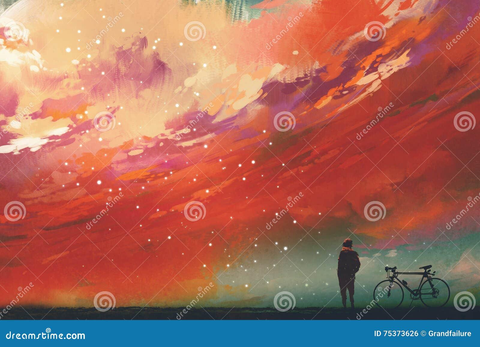 Mens met fiets die zich tegen rode wolken in de hemel bevinden