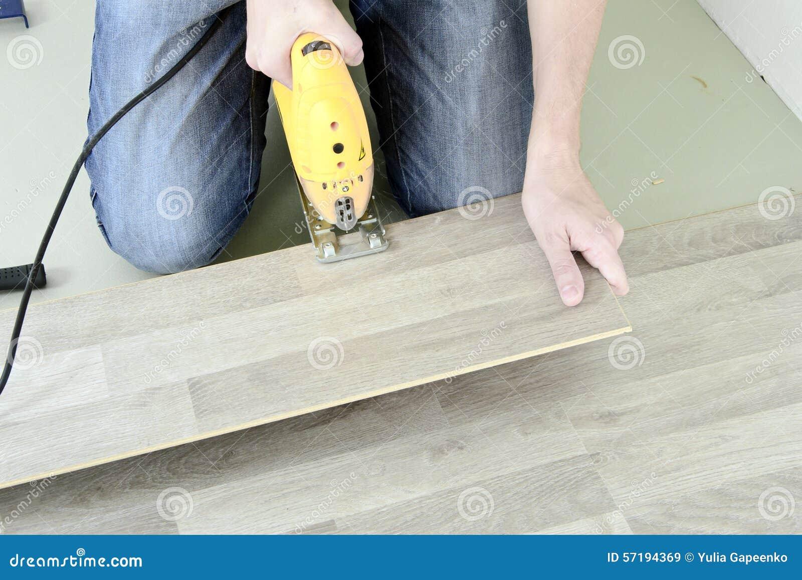 Mens met hulpmiddelen aan het leggen van laminaat stock afbeelding