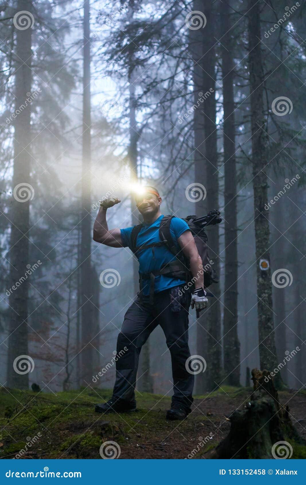 Mens met koplamp en rugzak in het bos
