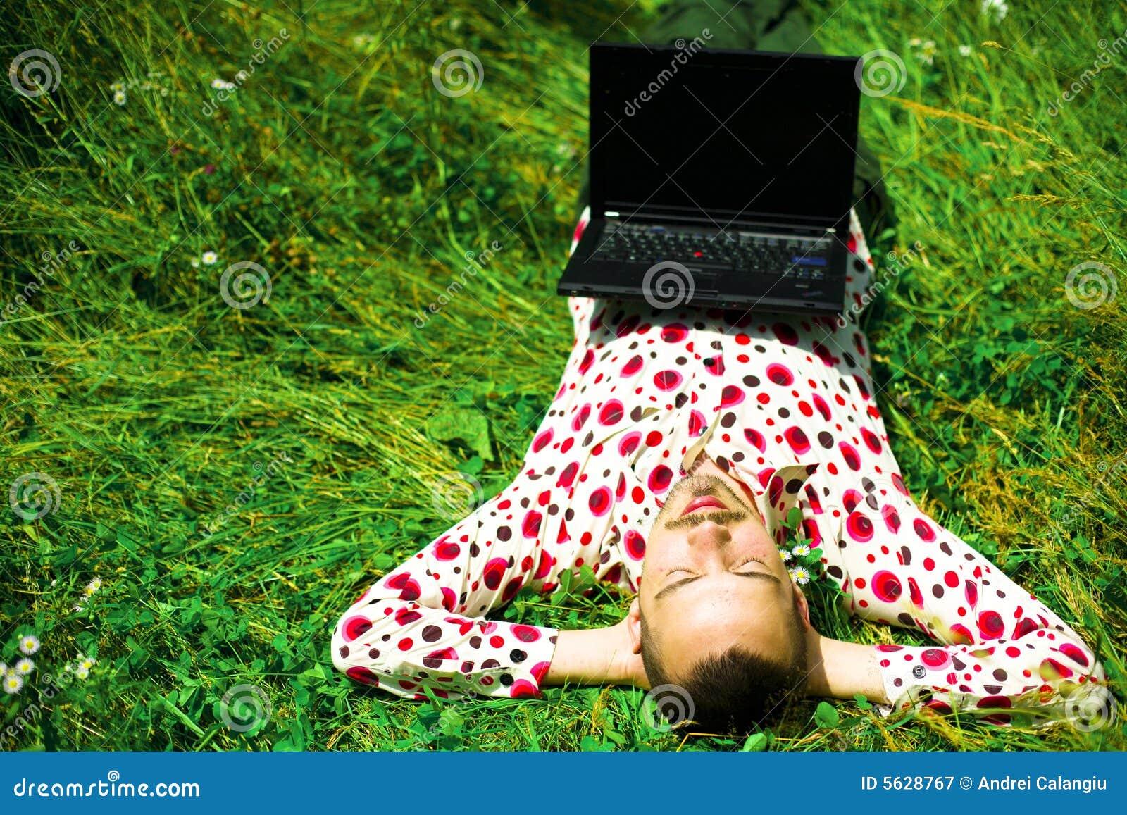Mens met laptop op gras