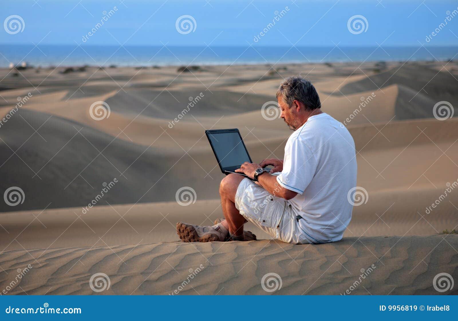 Mens met laptop zitting in woestijn.