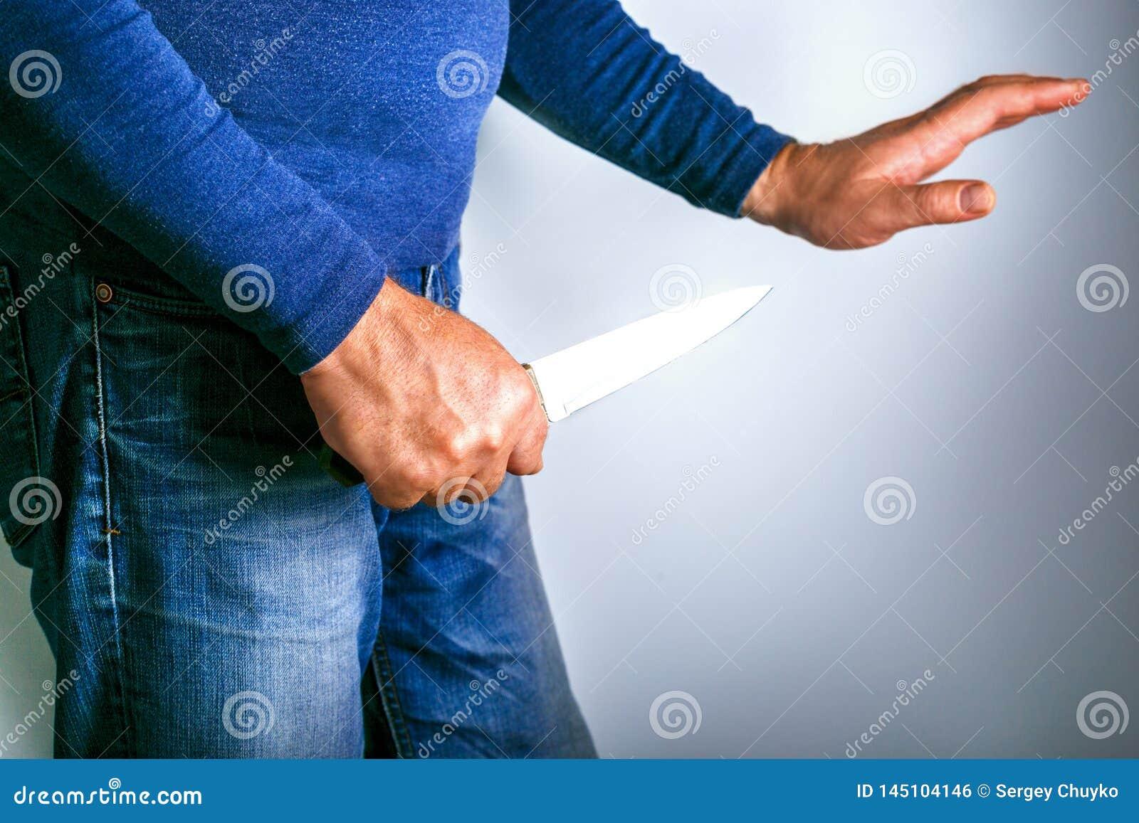 Mens met mes en hand bij gebaar van verzoening Conflictgeweld