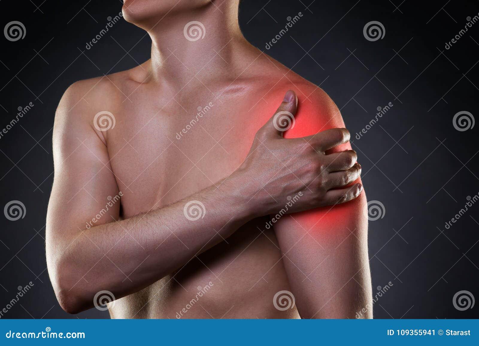Mens met pijn in schouder op zwarte achtergrond