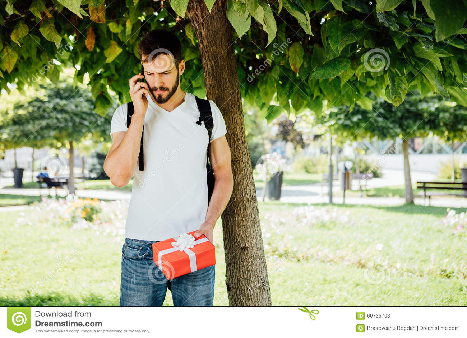 Mens met rugzak en een gift naast een boom