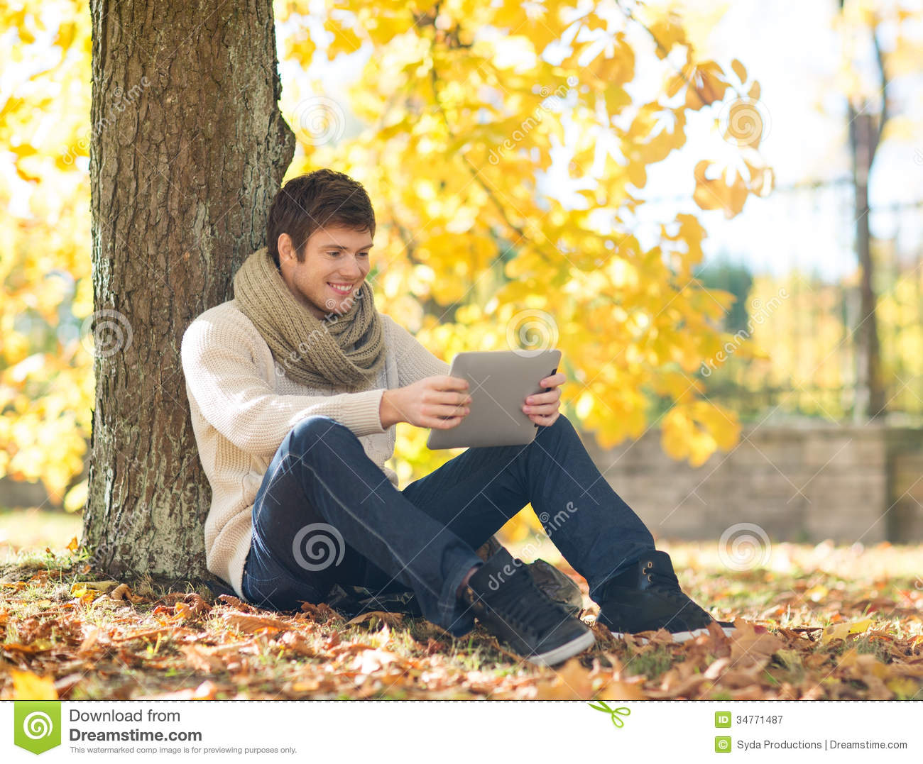 Mens met tabletpc in de herfstpark