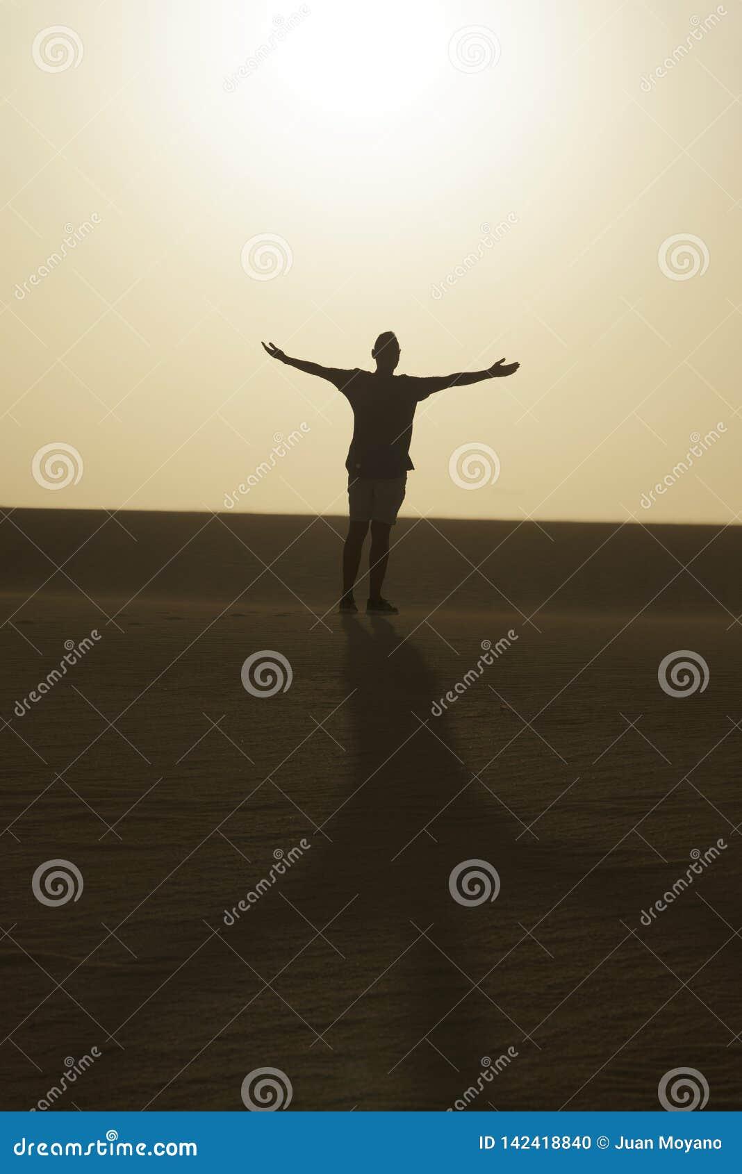 Mens met zijn wapens open in de lucht, in de woestijn