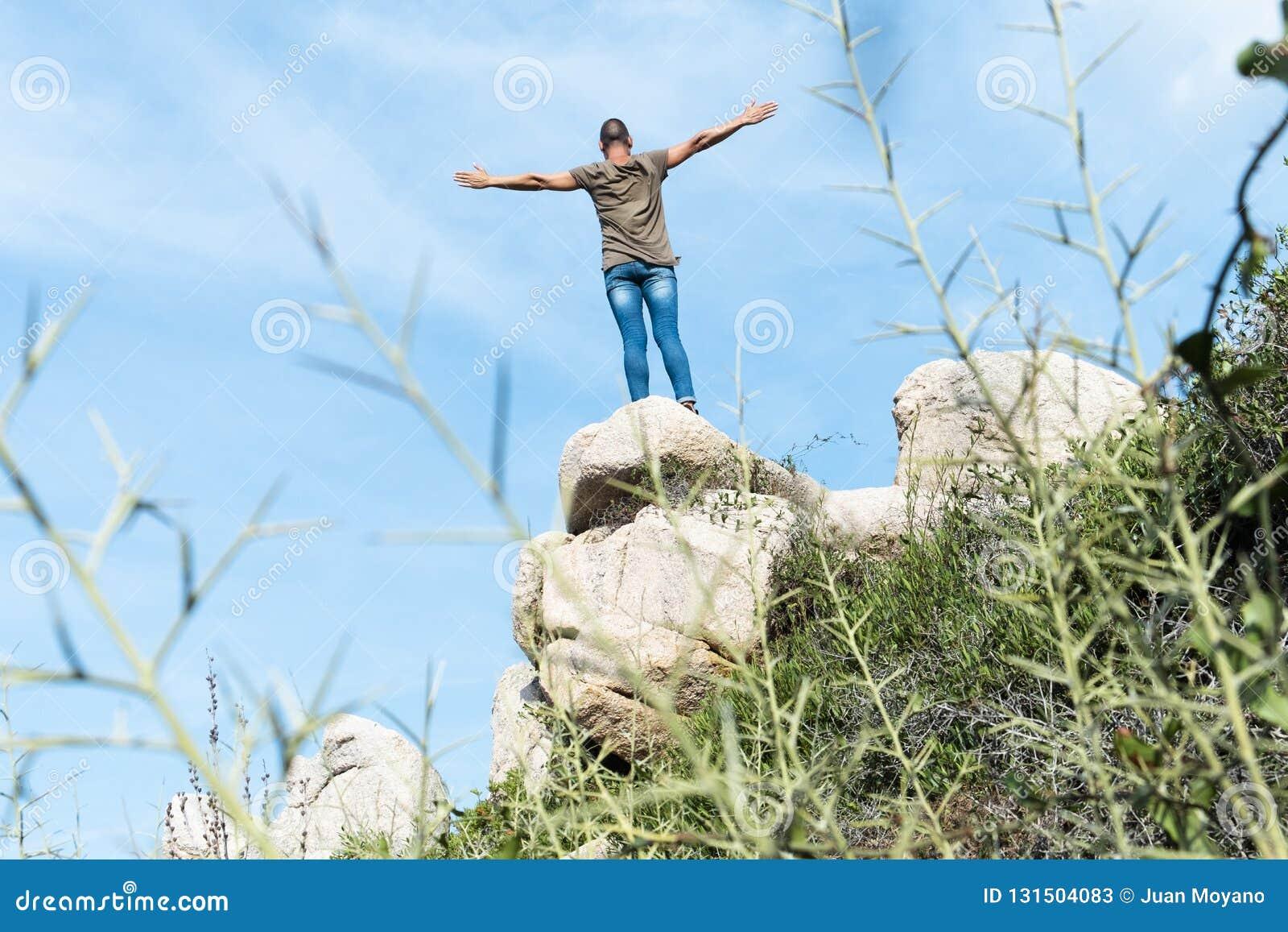 Mens op de bovenkant van een rotsvorming met zijn wapens in de lucht