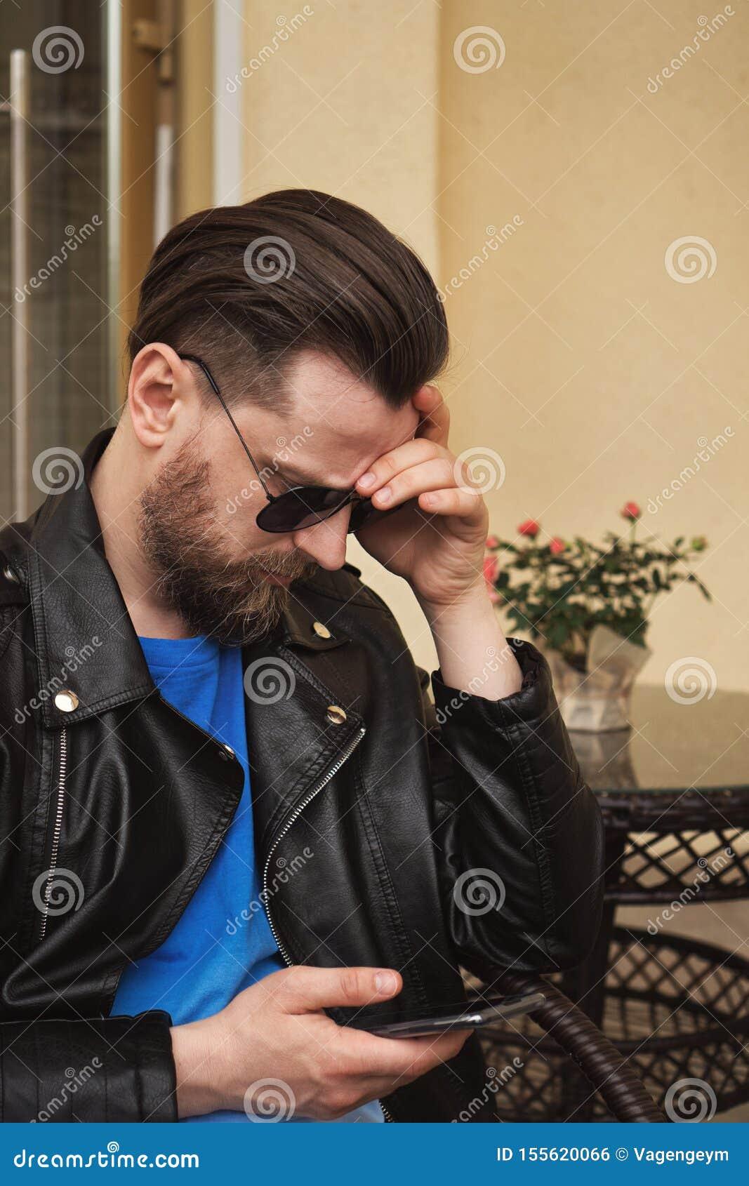 In mens op de koffie van het de zomerterras met smartphone