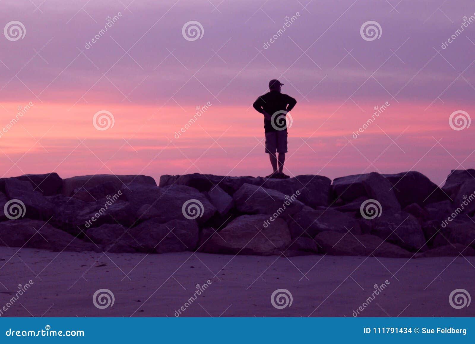 Mens op een Roze letten en Violet Sunset die bij het Strand