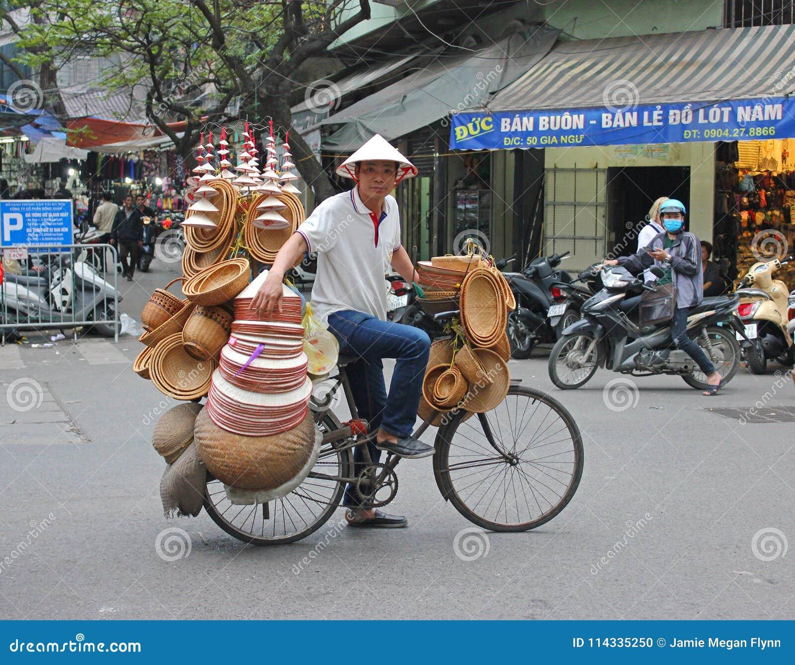 Mens op fiets die de hoeden van Hanoi verkopen