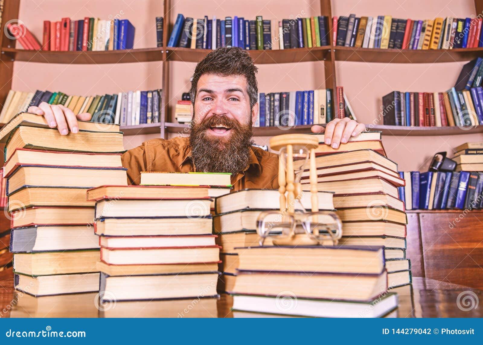 Mens op gelukkig gezicht tussen stapels van boeken, terwijl het bestuderen in bibliotheek, boekenrekken op achtergrond Leraar of