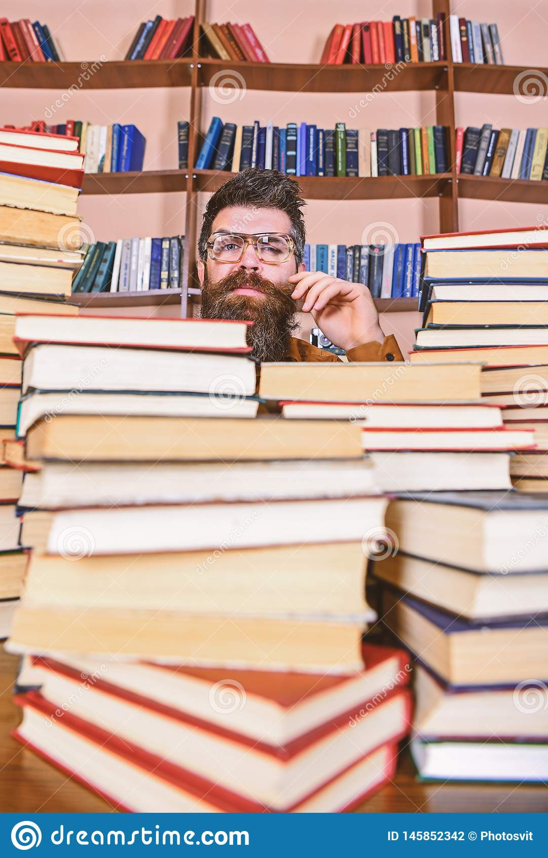 Mens op nadenkend gezicht tussen stapels van boeken in bibliotheek, boekenrekken op achtergrond De leraar of de student met baard