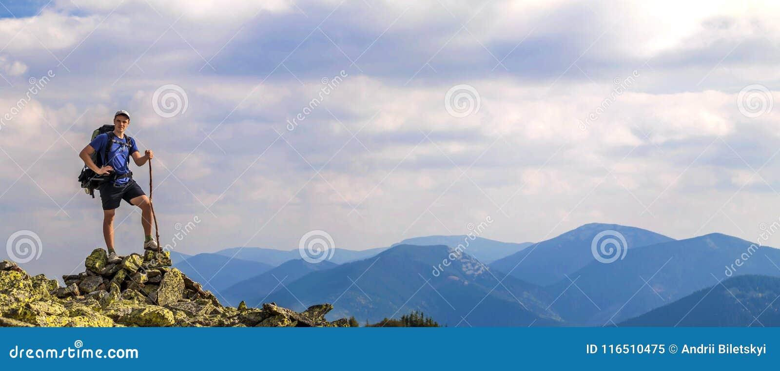 Mens op piek van berg Emotionele scène Jonge mens met backpac