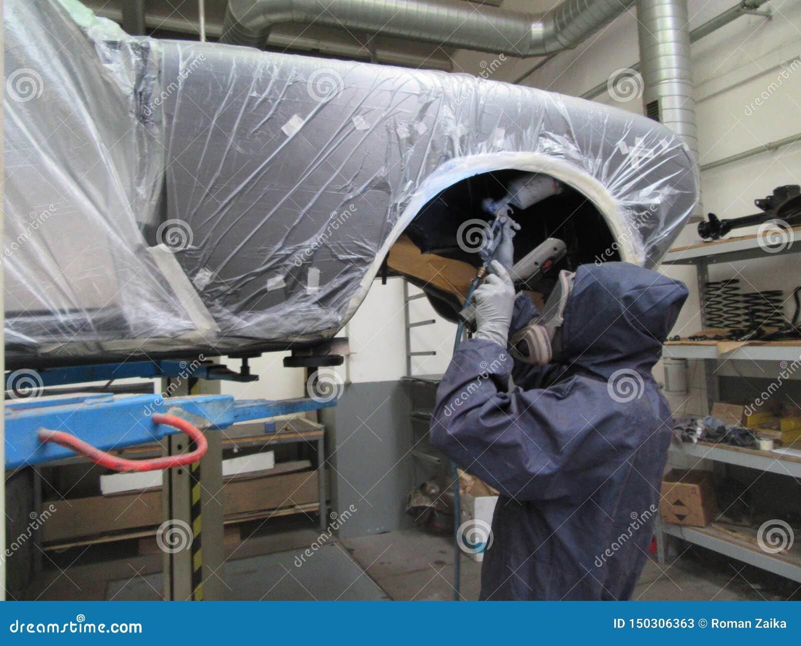 Mens in overtrek het schilderen auto in verfgarage