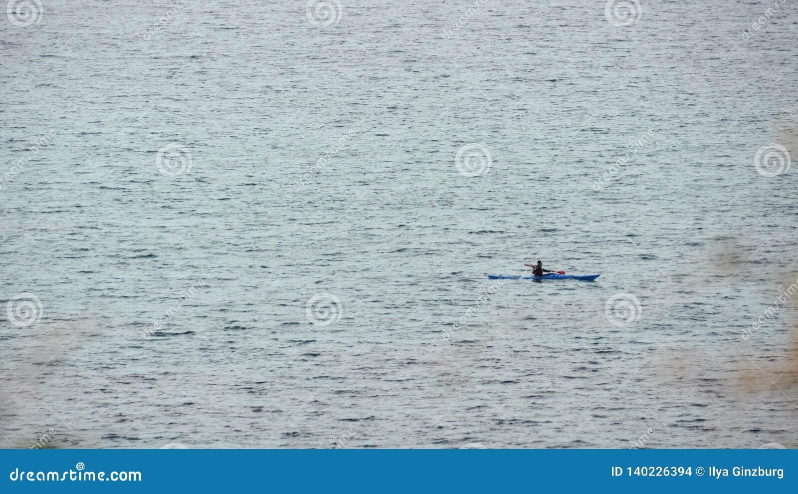 Mens in rijboot bij open zee