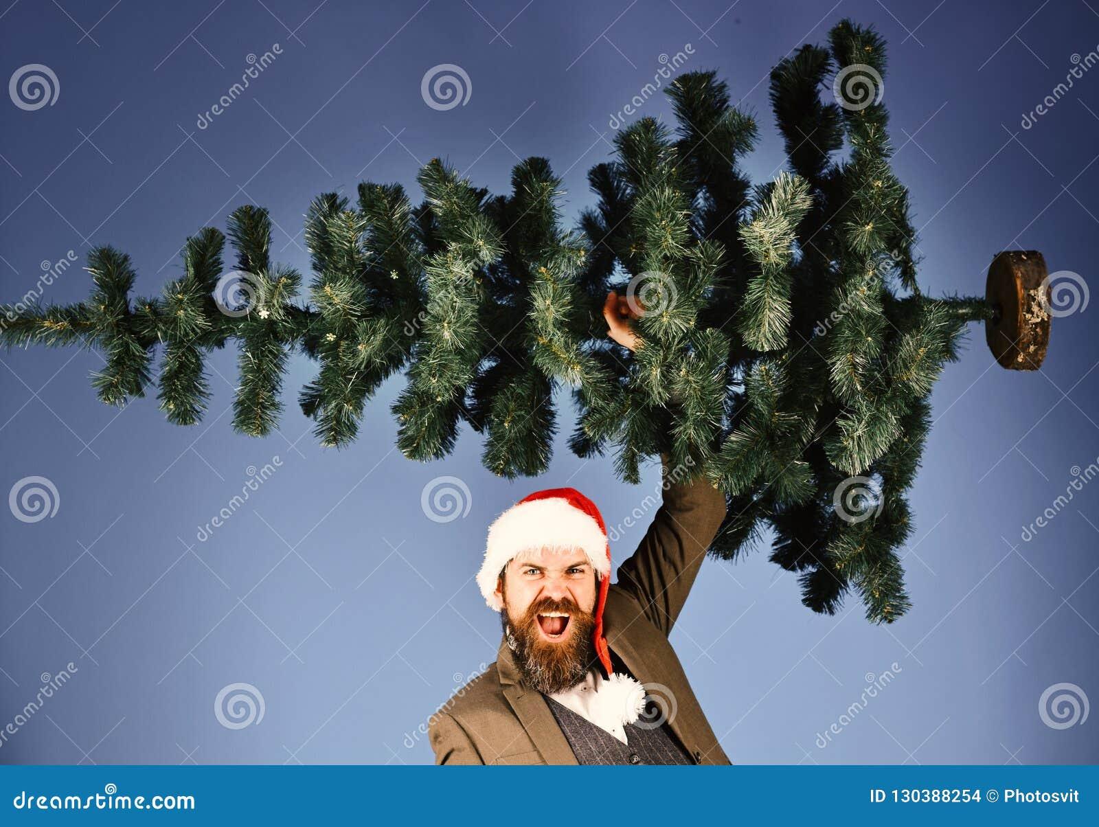 Mens in slim kostuum en Kerstmanhoed op blauwe achtergrond