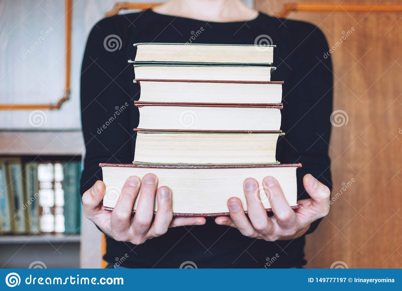 Mens, Student die vele boeken in handen op de achtergrond van boekenrekken houden De mannelijke handen houden een grote stapel bo