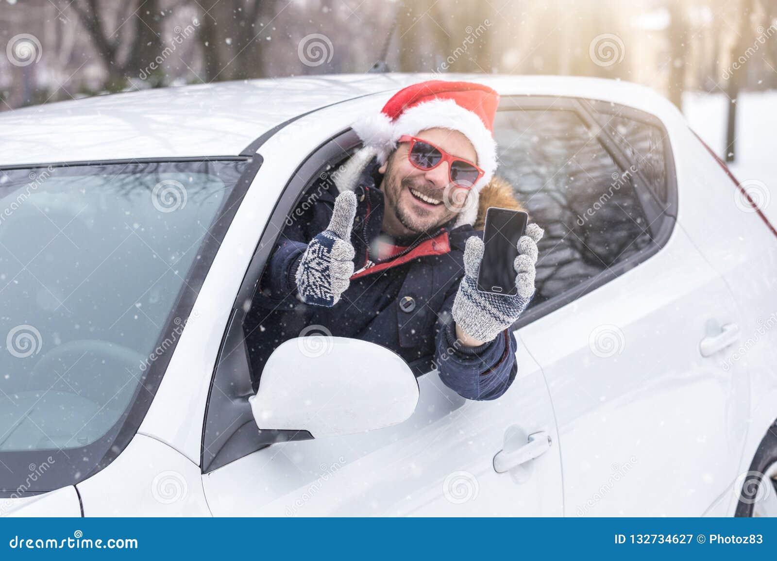 Mens uit autoraam die Santa Claus-hoed dragen en lege het scherm slimme telefoon houden
