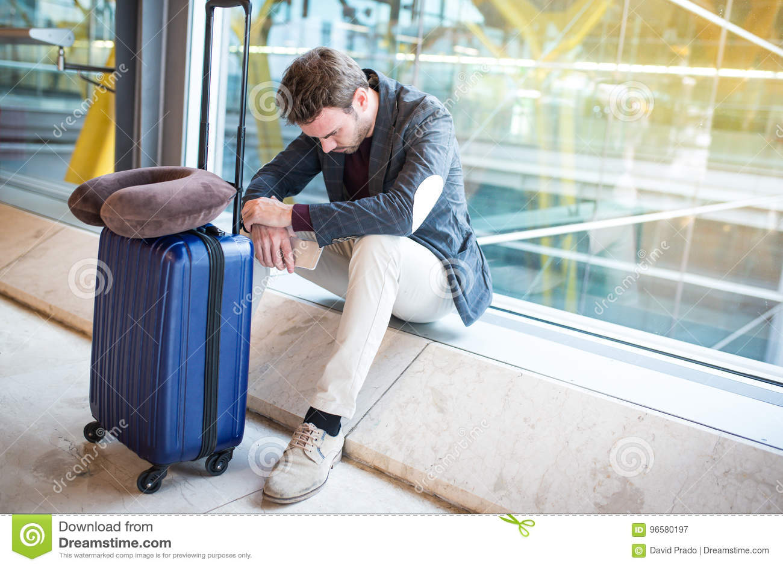 Mens verstoord, droevig en de boos bij de luchthaven wordt zijn vlucht vertraagd
