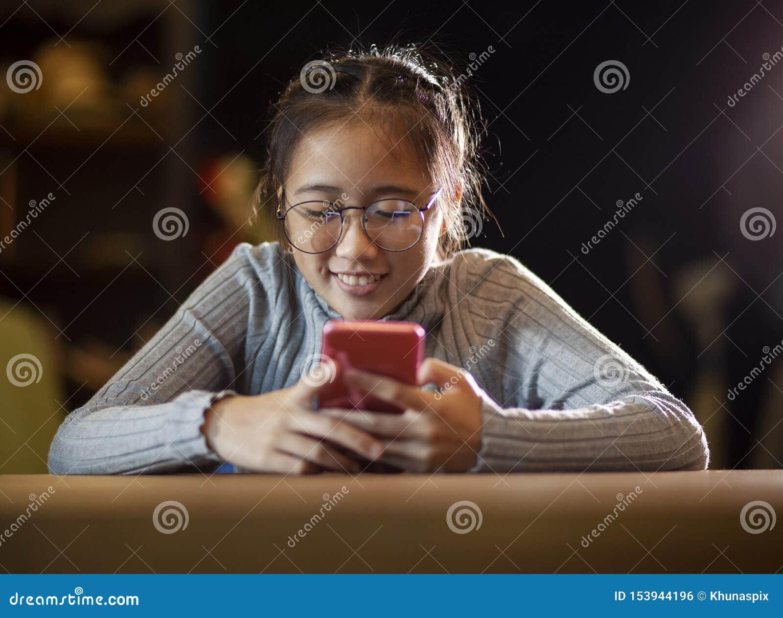 Mensagem asiática da leitura do adolescente na tela esperta do telefone com a cara de sorriso da felicidade