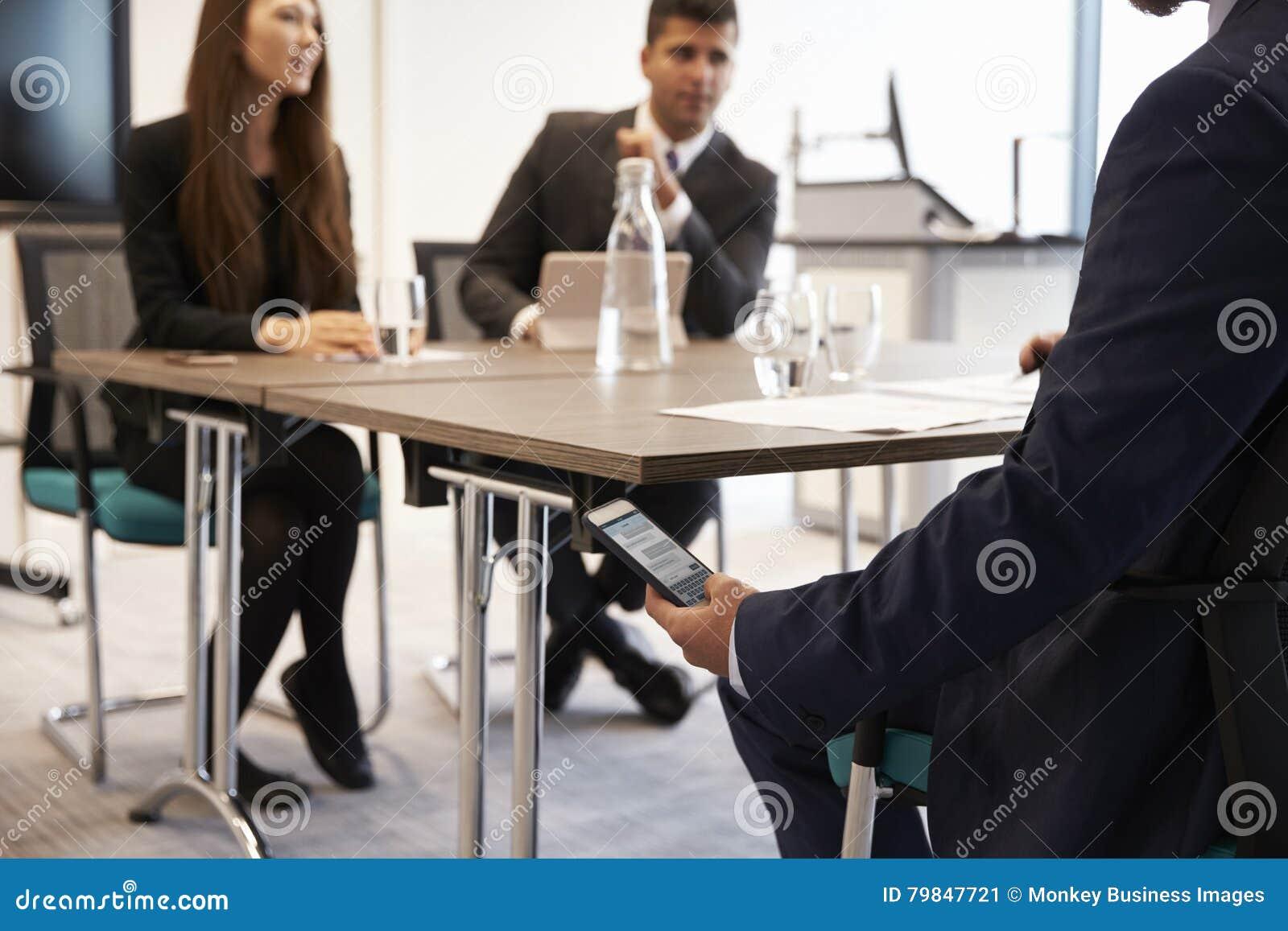 Mensagem de Discreetly Receiving Text do homem de negócios durante a reunião