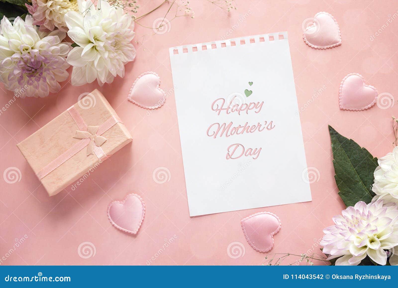 Mensagem do cumprimento do dia de mães com dálias e caixa de presente em um rosa