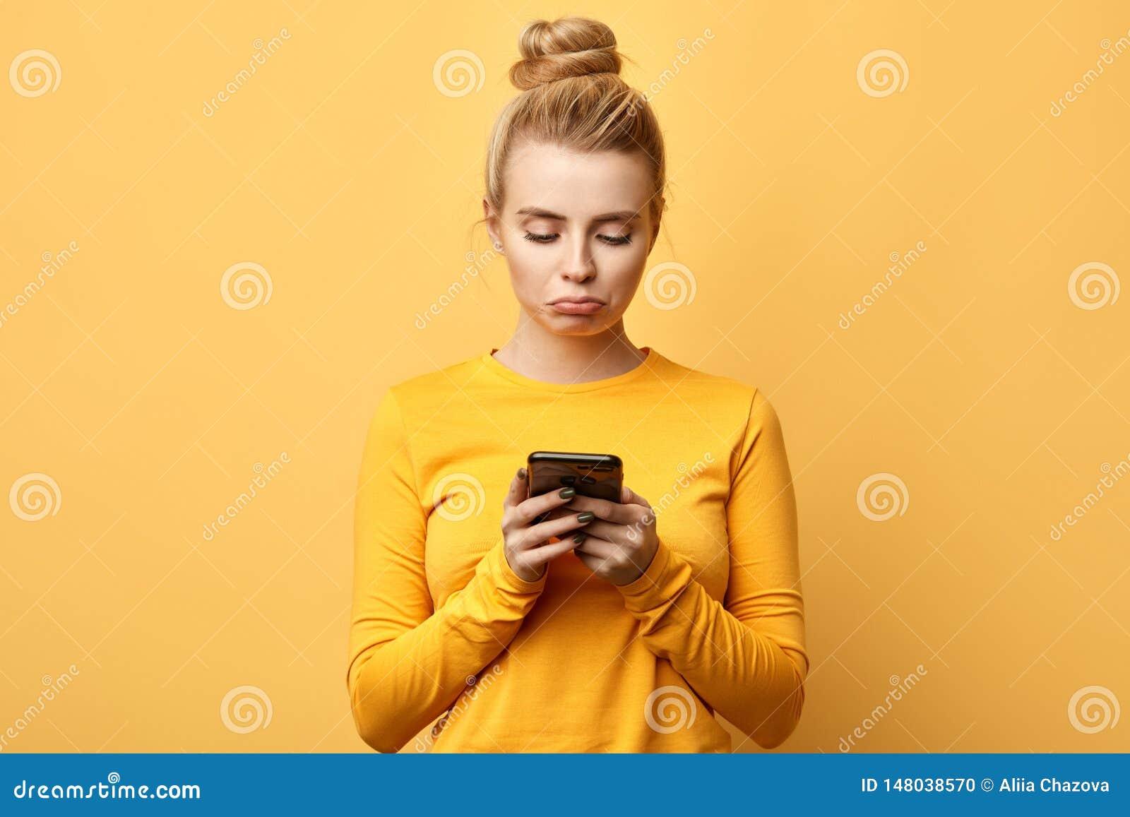 Mensagem infeliz desapontado virada da leitura do telefone celular da terra arrendada da menina