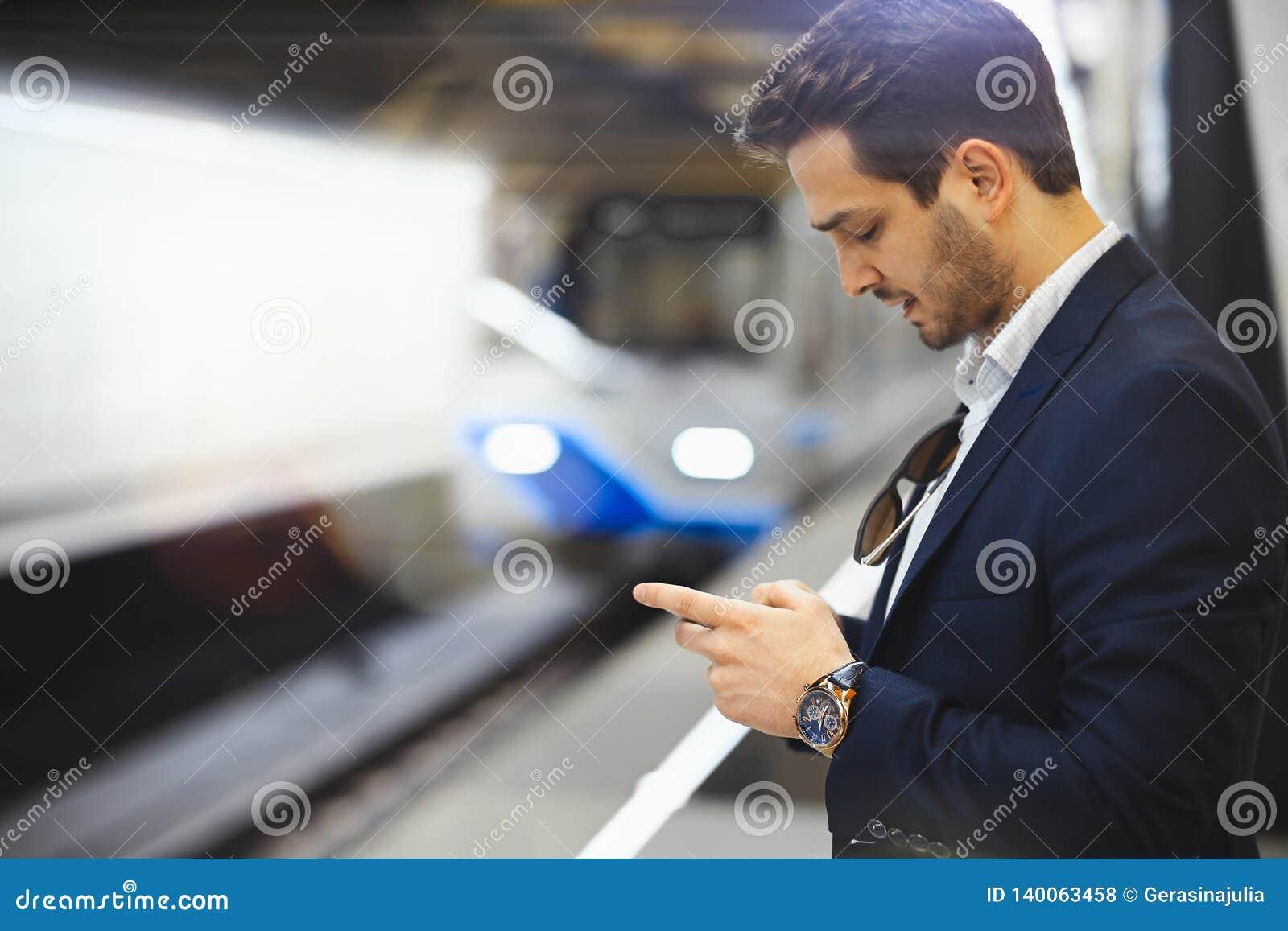 Mensagem texting do homem de negócios atrativo no telefone celular ao esperar o trem no metro