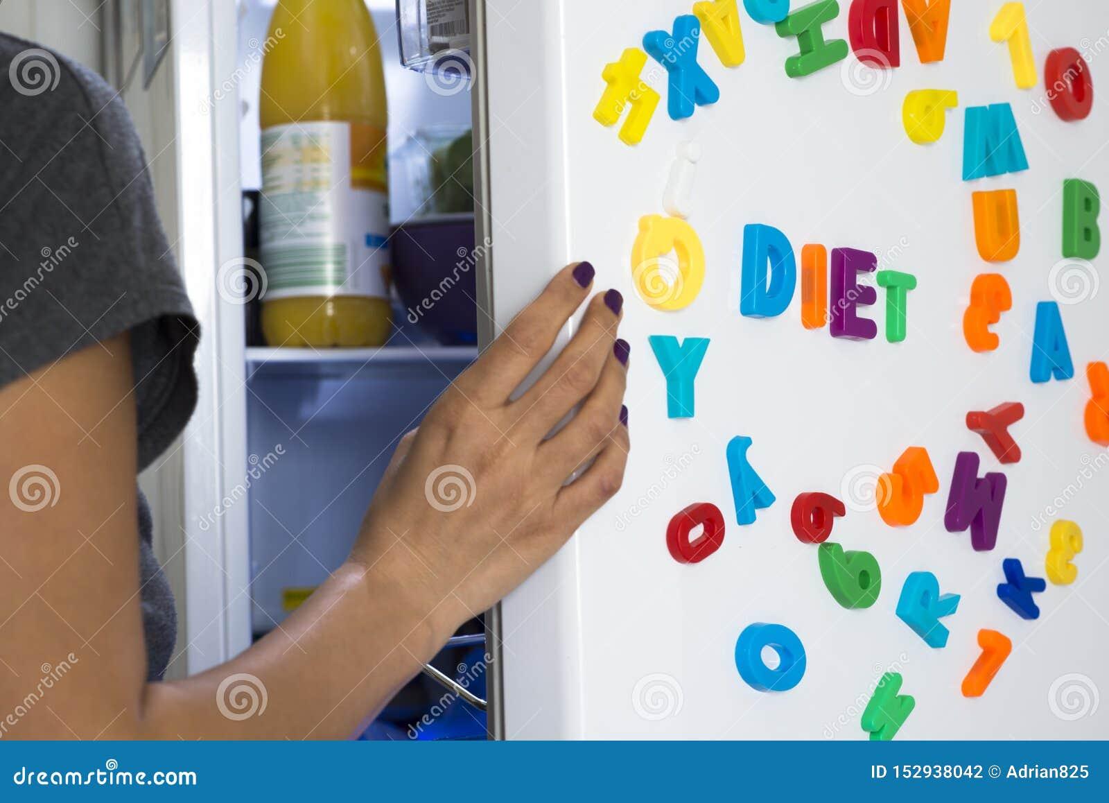 Mensaje de la dieta de letras coloridas en el refrigerador blanco con la mujer hambrienta que mira dentro