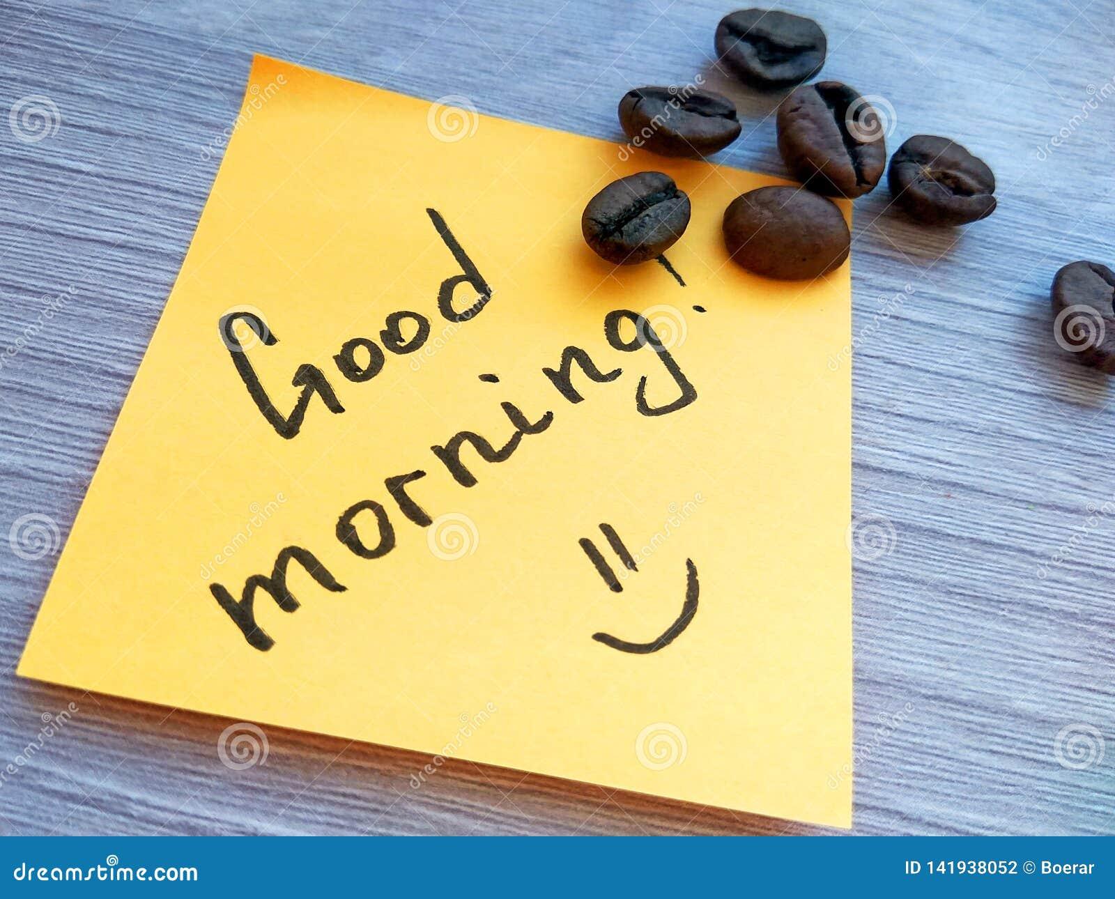 Mensaje manuscrito de la buena mañana en nota pegajosa anaranjada con los granos de café en fondo de madera
