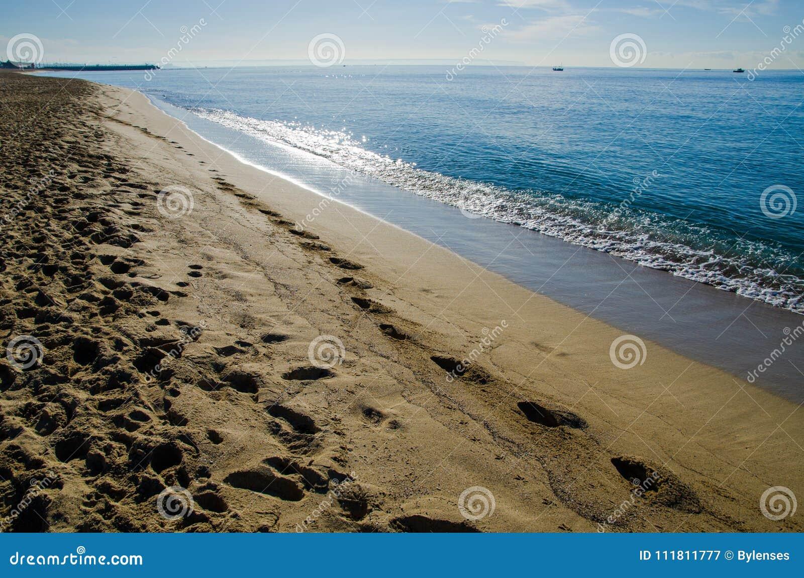 Menschliche Abdrücke auf einem sandigen Strand in Palma de Mallorca, Spanien