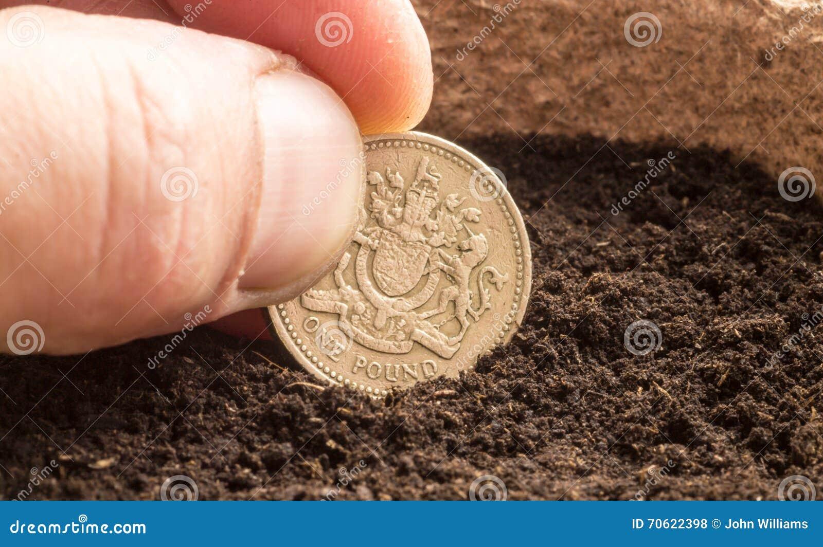Menschliche Hand Die Eine Pfund Münze Im Kompost Sät Stockfoto