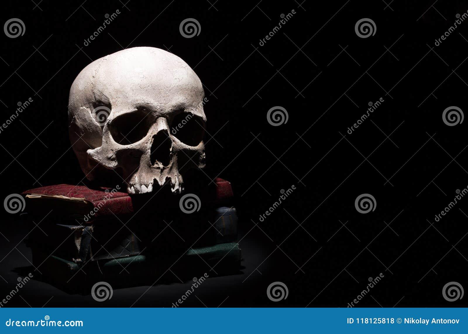 Menschlicher Schädel auf alten Büchern auf schwarzem Hintergrund unter Lichtstrahl Drastisches Konzept