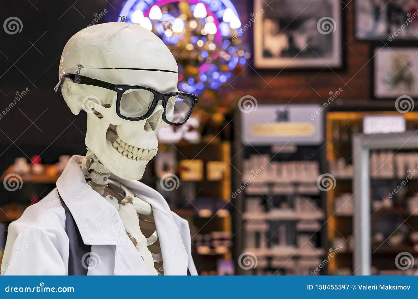 Menschliches Skelett in einem weißen medizinischen Kleid und in schwarzen Gläsern