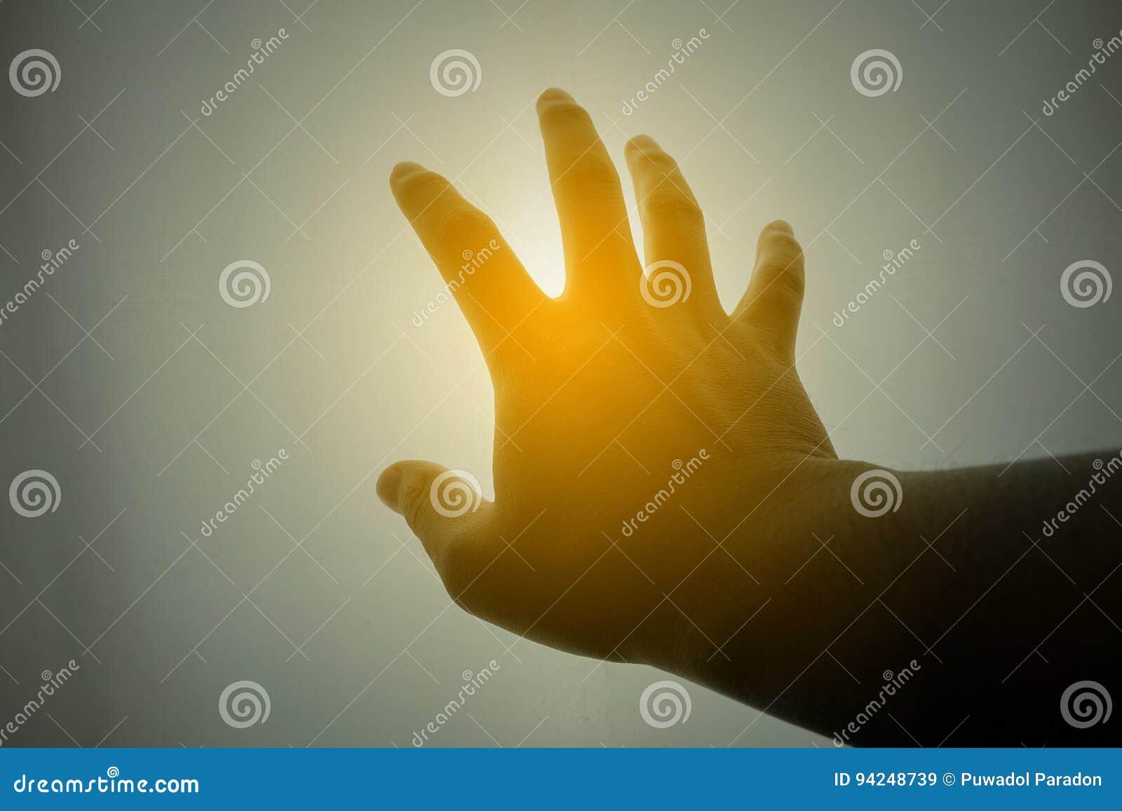 Menselijke hand die voor de zon bereiken