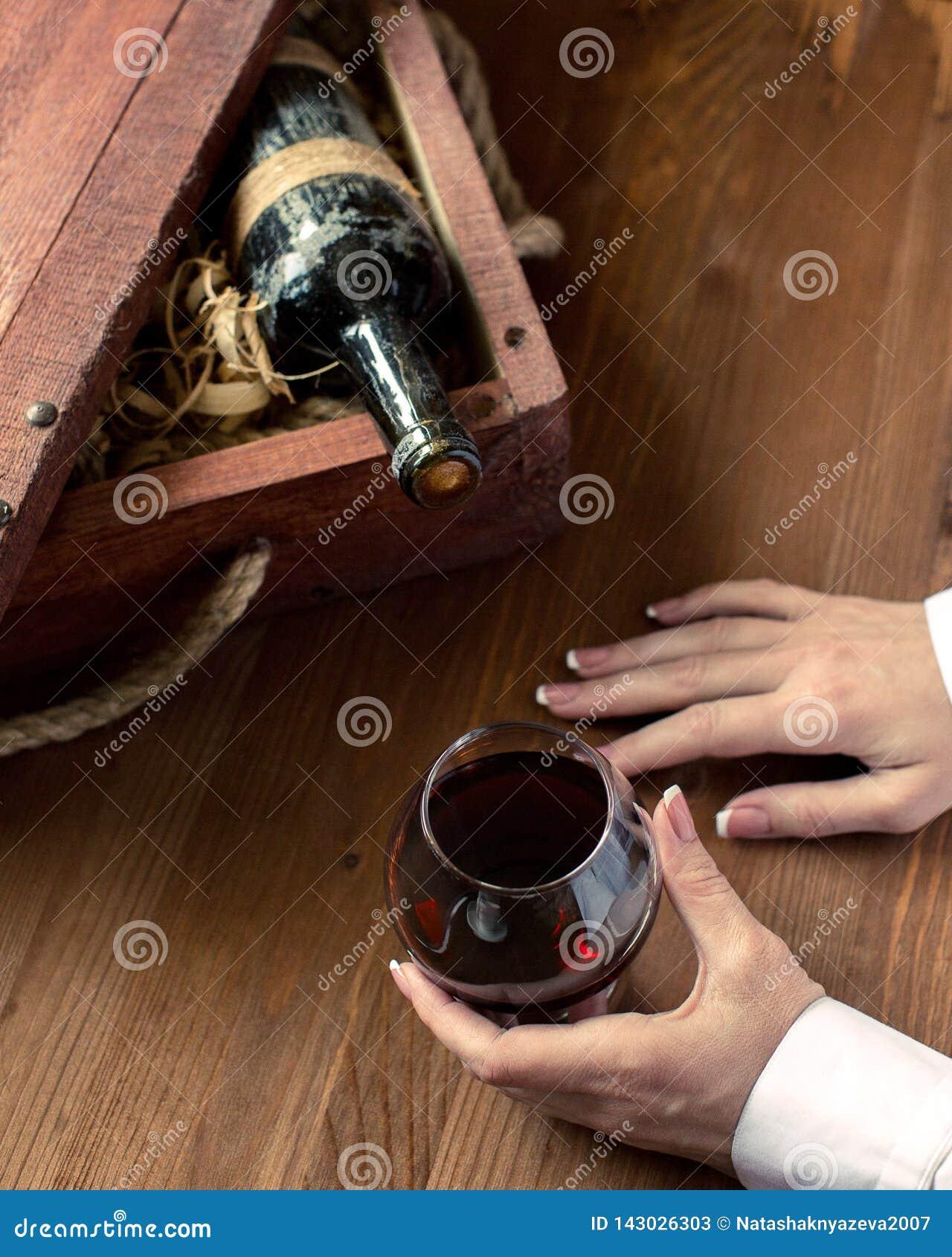 Menselijke hand met een kop van rode wijn Oude fles in uitstekend krat onder het houten scheren op houten achtergrond, geselectee