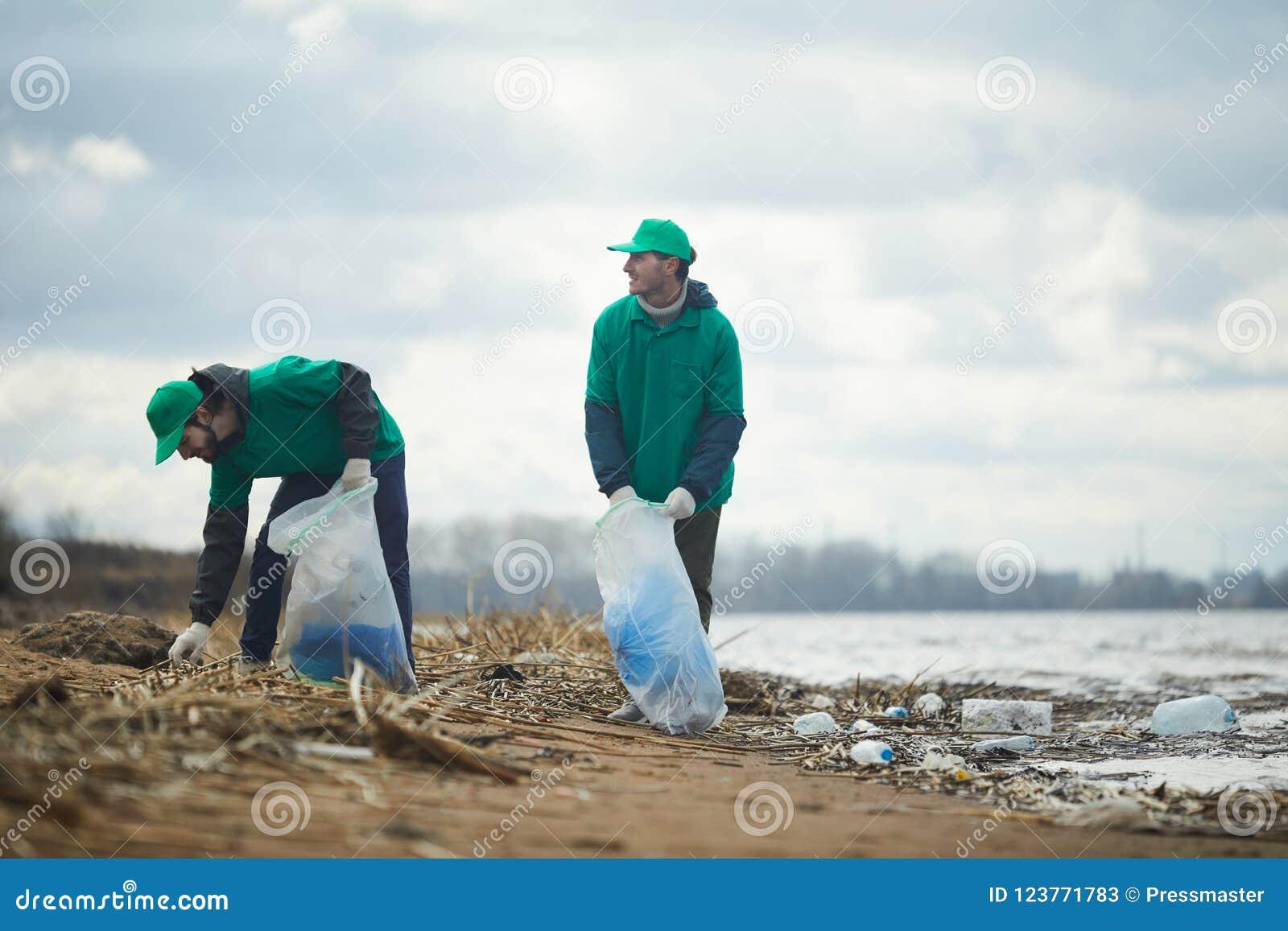Mensen die aan verontreinigde kust werken