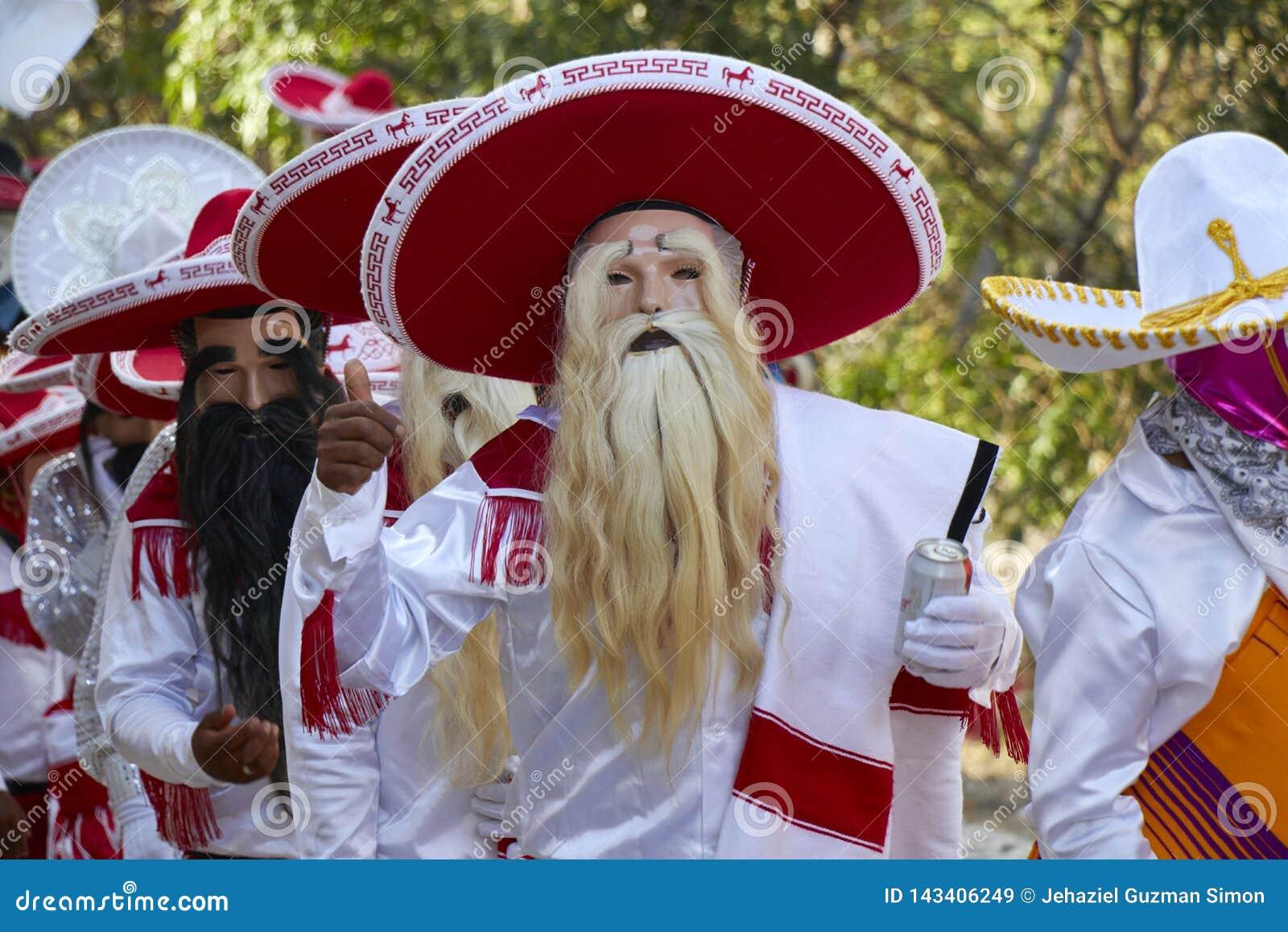 Mensen die als Mexicaanse charro of mariachi met een wit kostuum en maskers worden vermomd