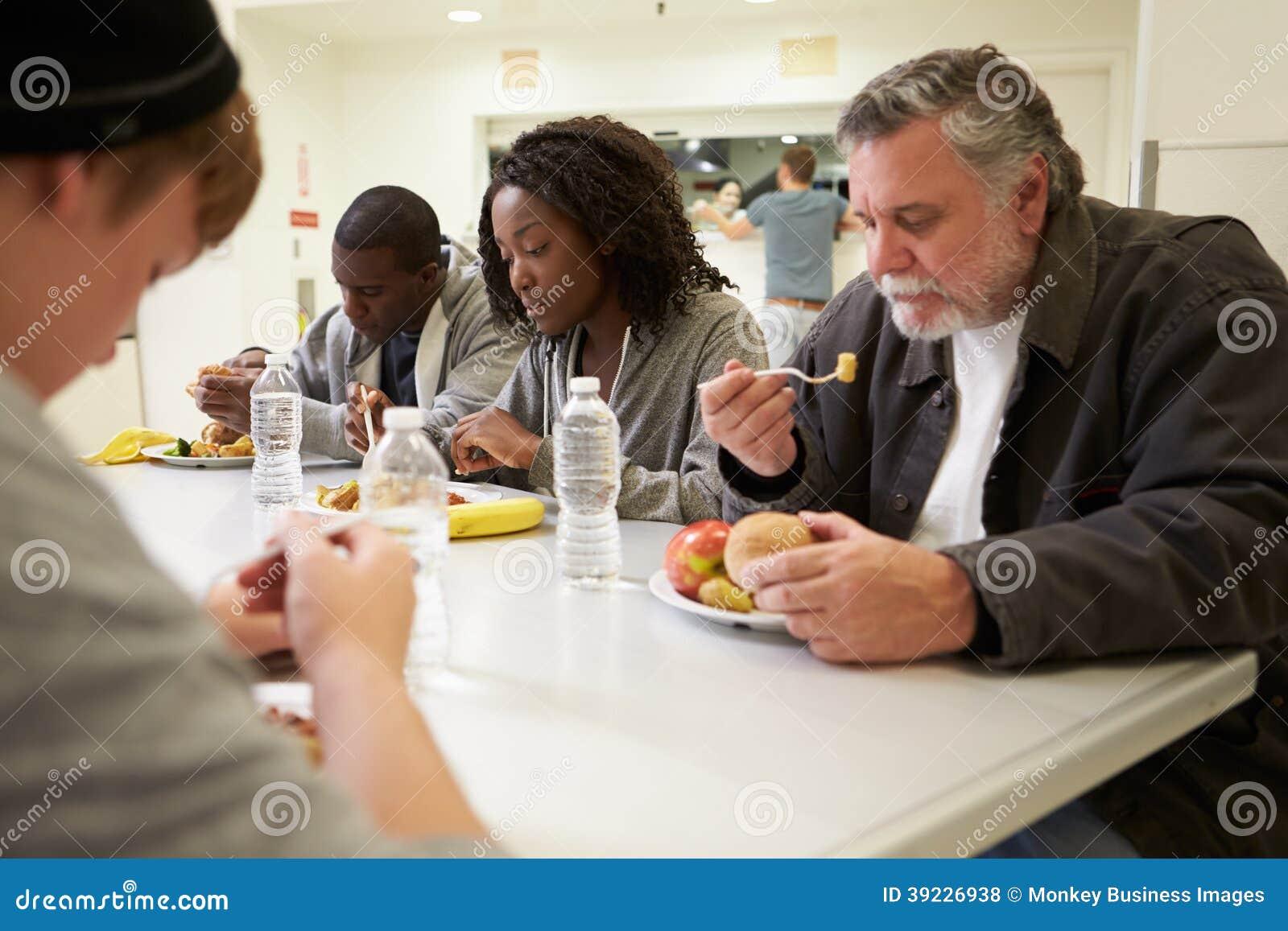 Mensen die bij Lijst zitten die Voedsel in Dakloze Schuilplaats eten