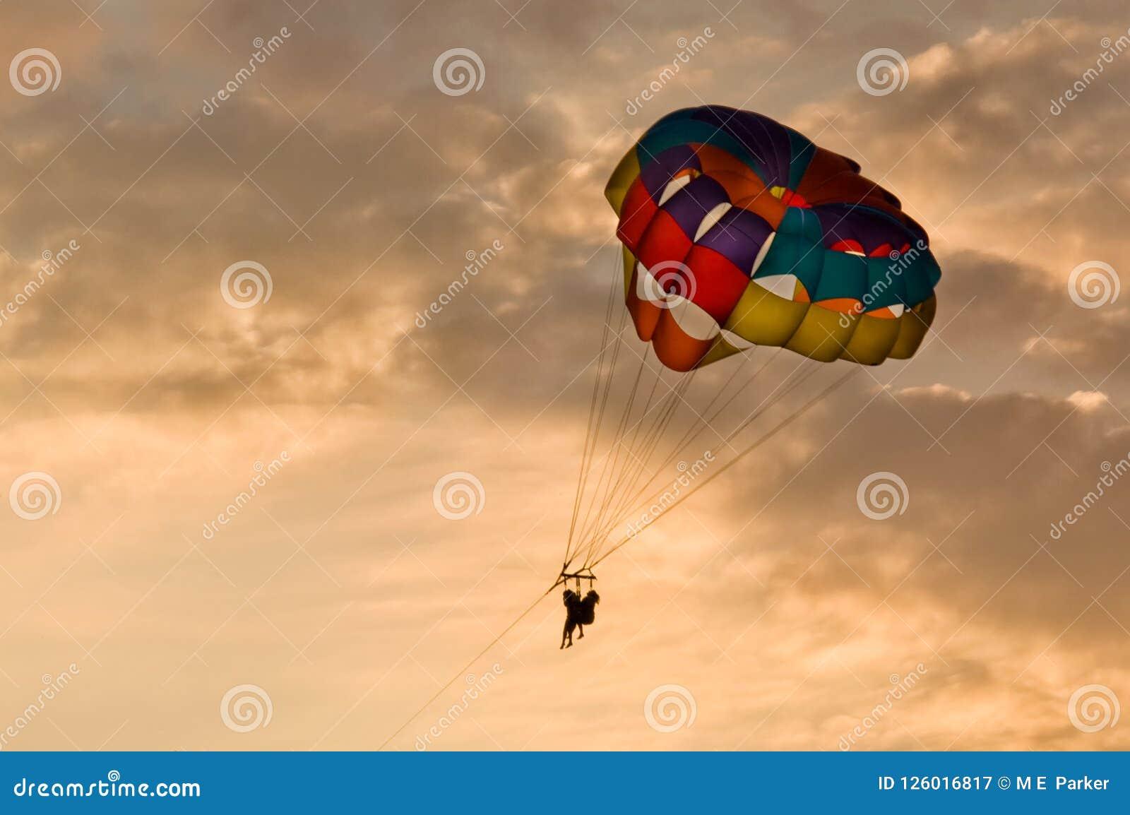 Mensen die bij zonsondergang in mooi licht parasailing