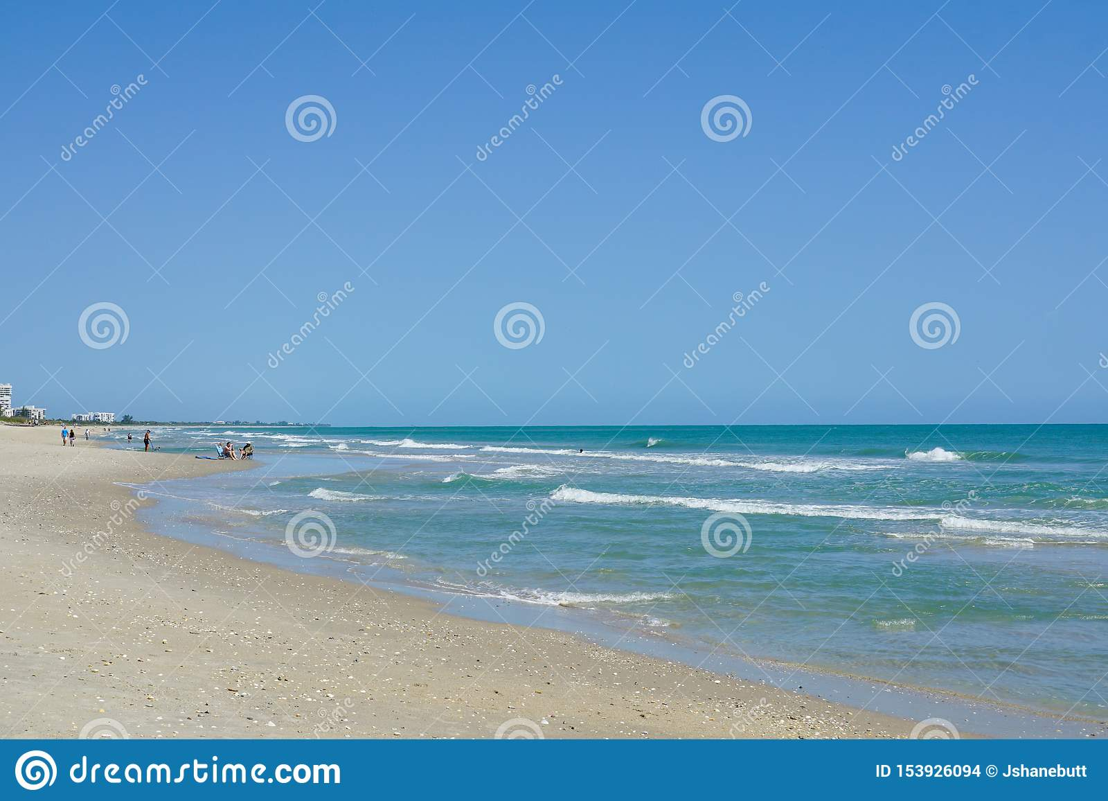 Mensen die en op het strand op het Eiland van het Noordenhutchinson, Florida lopen zitten