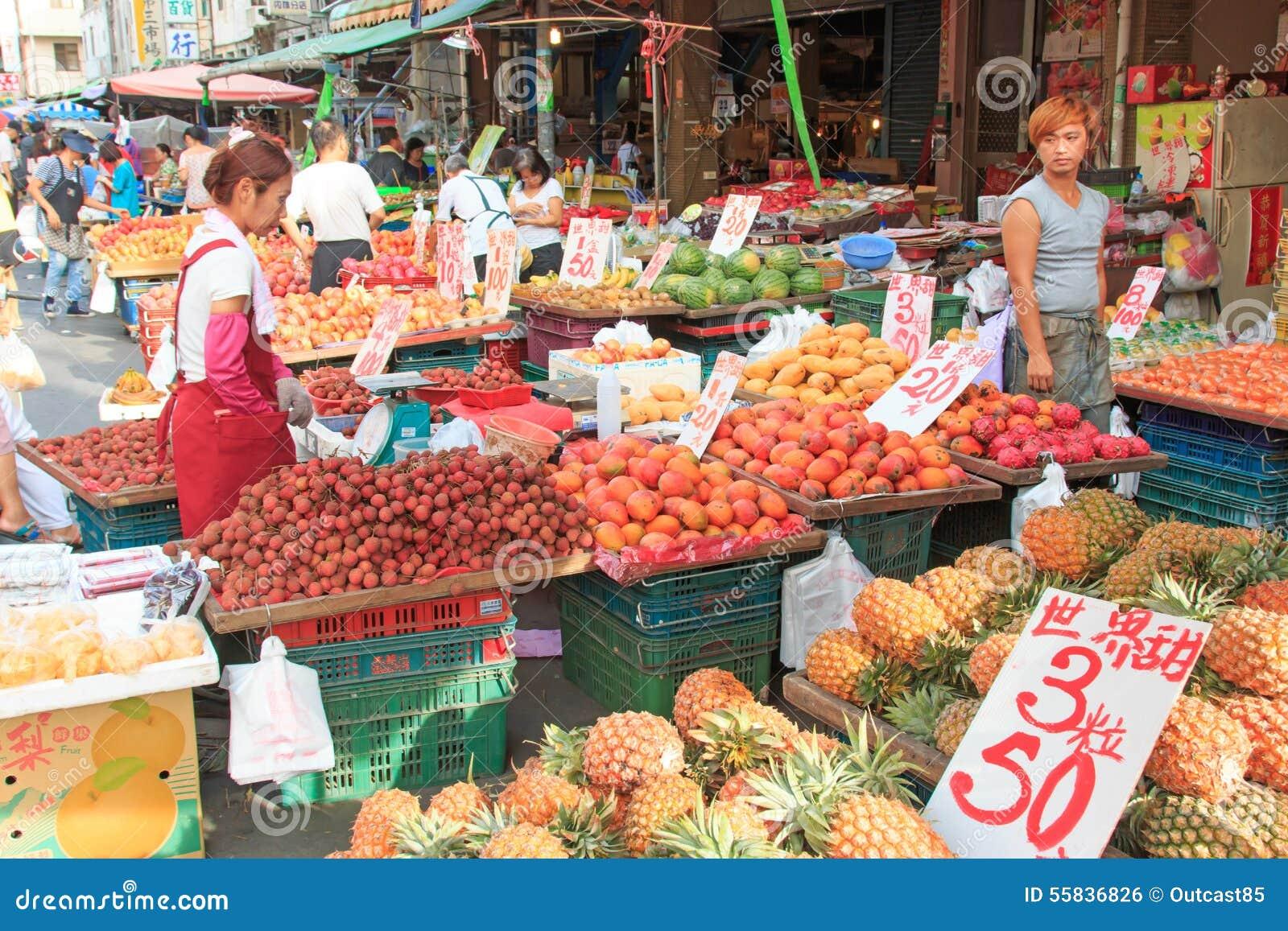 Mensen die en voedsel in een traditioneel fruit en een plantaardige markt van Taiwan verkopen kopen