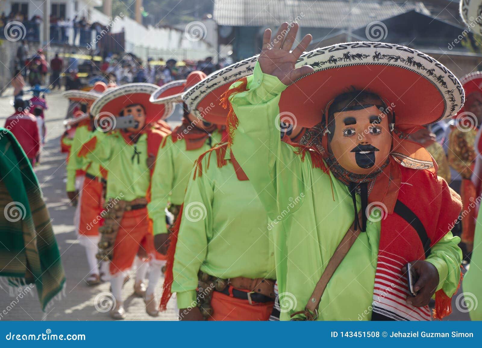 Mensen die, gebruikend maskers begroeten die, als mariachi met groene overhemden en oranje hoeden worden vermomd