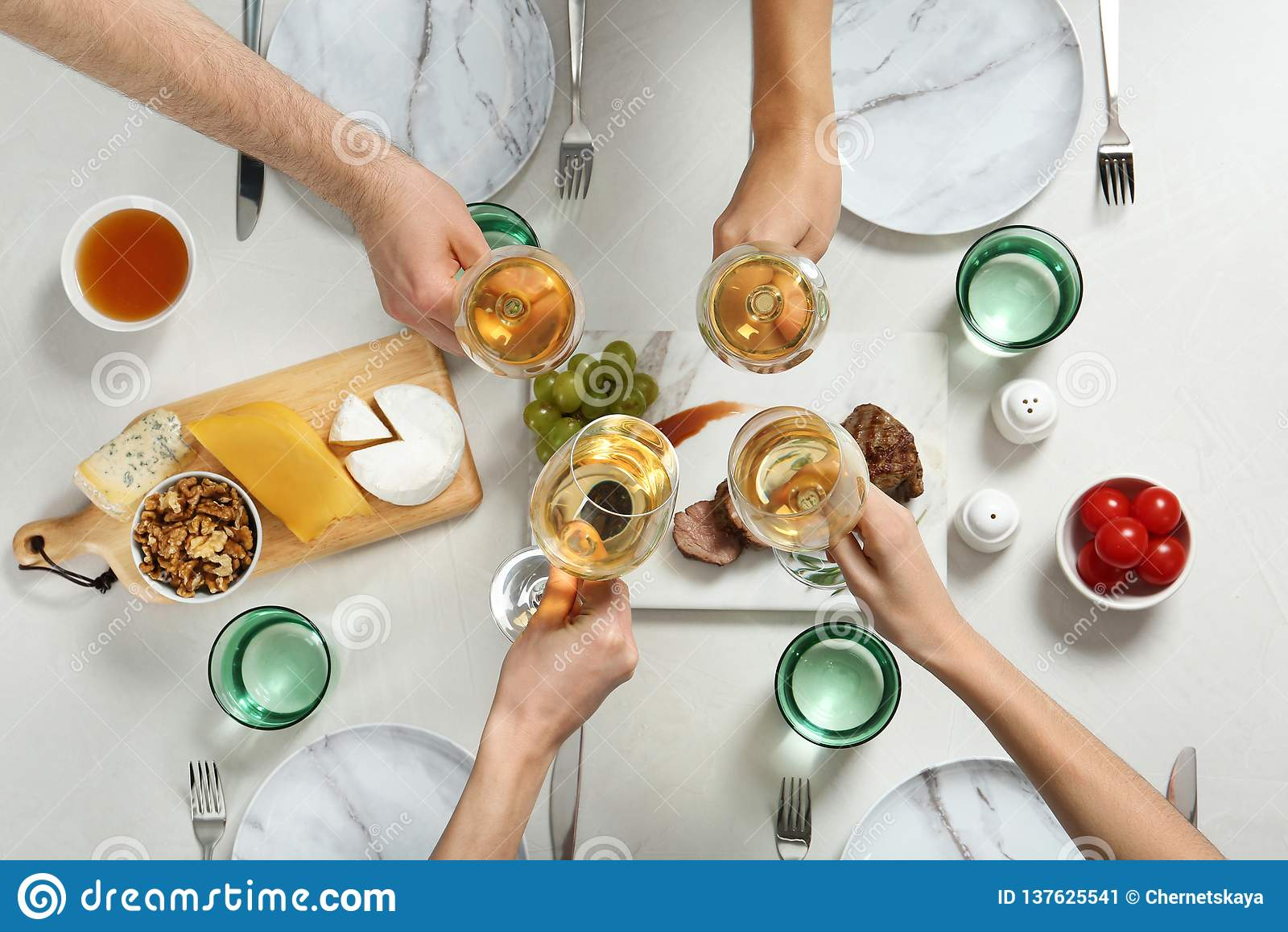 Mensen die glazen witte wijn over lijst met smakelijke snacks houden