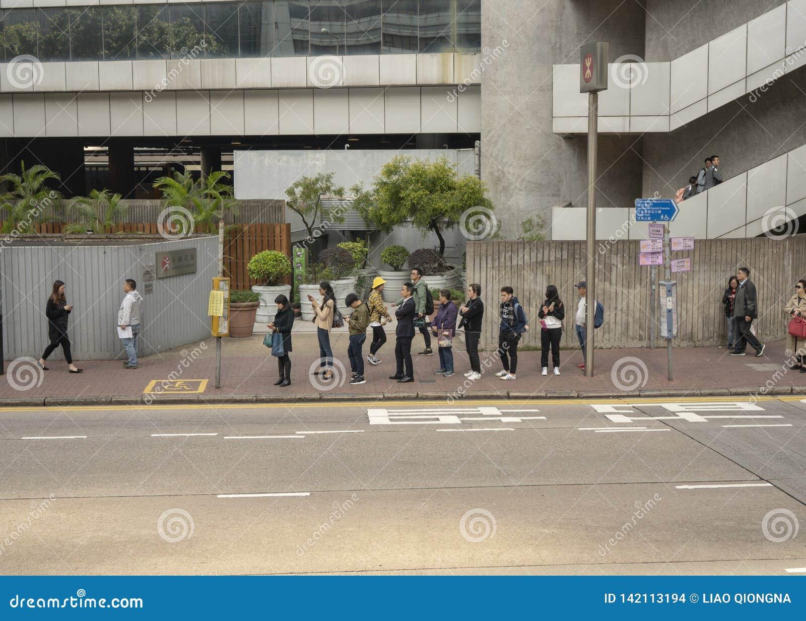 Mensen die in lijn op de bus wachten